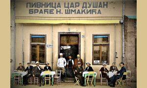 """Kafana """"Car Dušan"""", s desna na vratima Dobro Šmakić, do njega Vlajo i načelnik Kostadinović u uniformi. Za stolom desno sa naočarima Dragi Aranđelović koji je imao bioskop"""