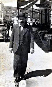 Dobro Šmakić ispred svoje kafane, a iza se vidi česma na Žitnom pijacu