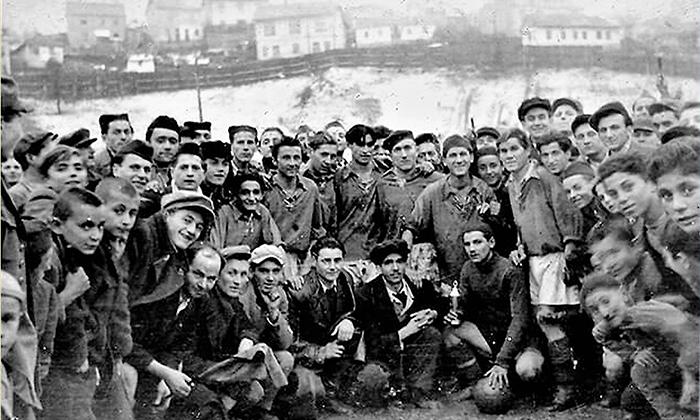 Fk Prvi Partizan na stadionu u Begluku tokom pedesetih godina 20. veka sa navijačima; Asan Dudić prvi u dresu s leva