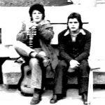 Bas i Kovač na kamenoj klupi na Trgu krajem hladnjikavog kišnog leta 1971. godine